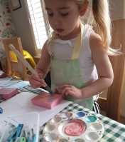 Belle painting her block.